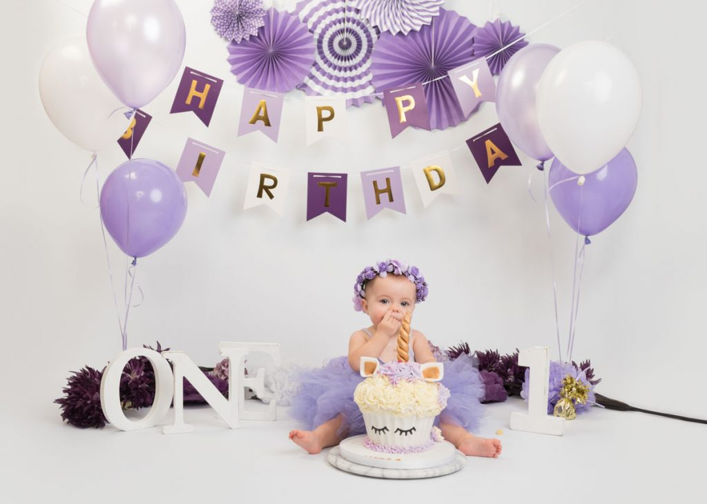 purple themed first birthday with a unicorn cake