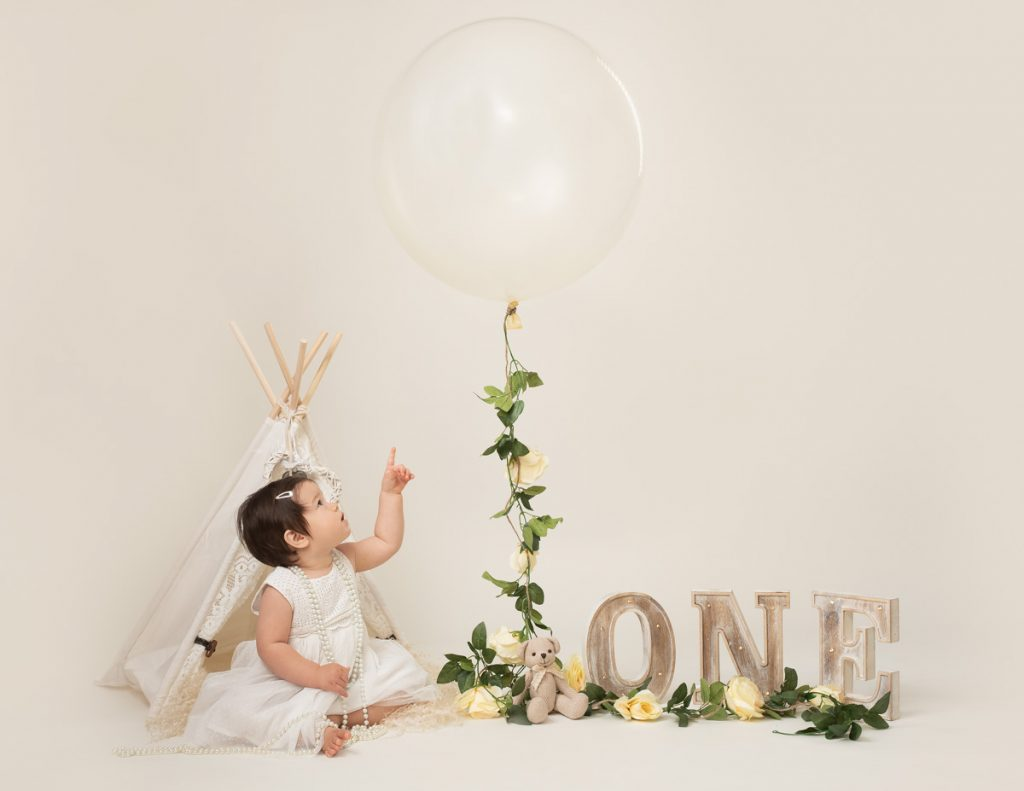 baby pointing to a balloon