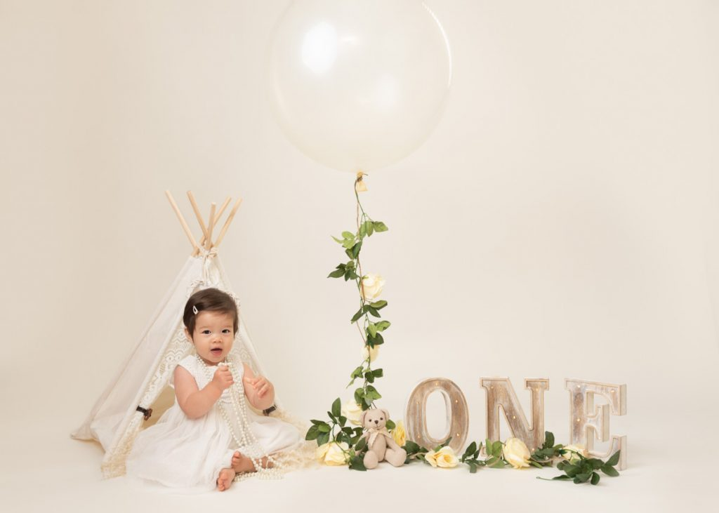 massive balloon and a clean cream and white setting for baby sitter and birthday shoot