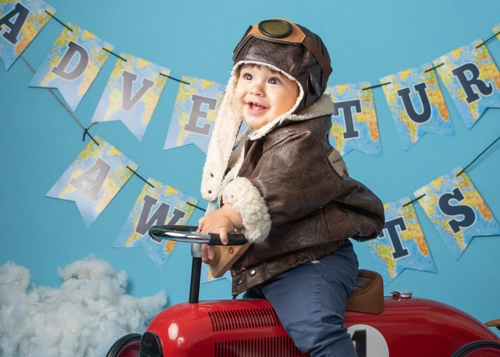adventure awaits first birthday boy on a car wearing a cool outfit