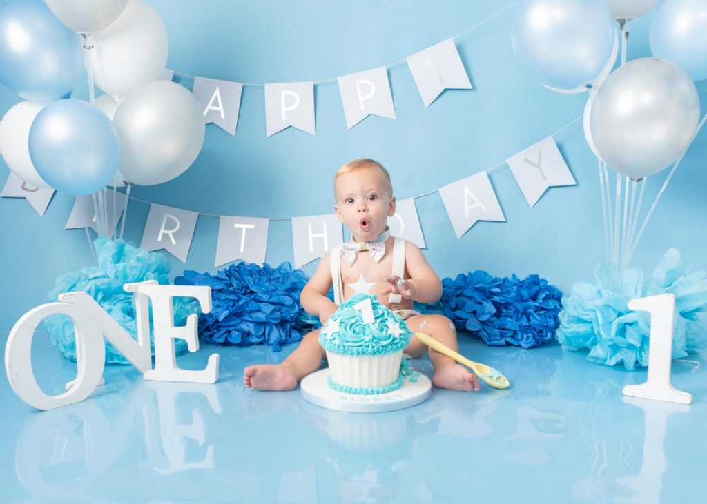 little boy eating his icing off his cake first birthday shoot