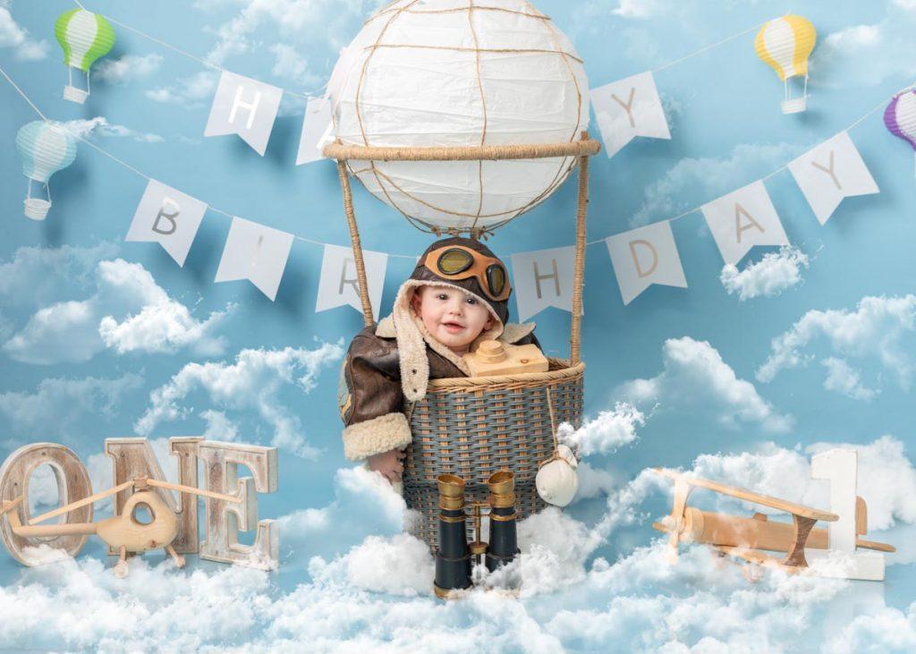 little boy in a hot air balloon first birthday shoot