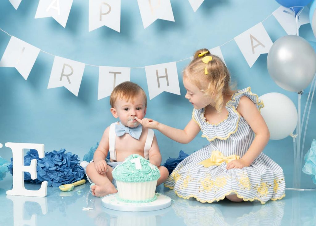 sister feeding her brother some of his first birthday cake