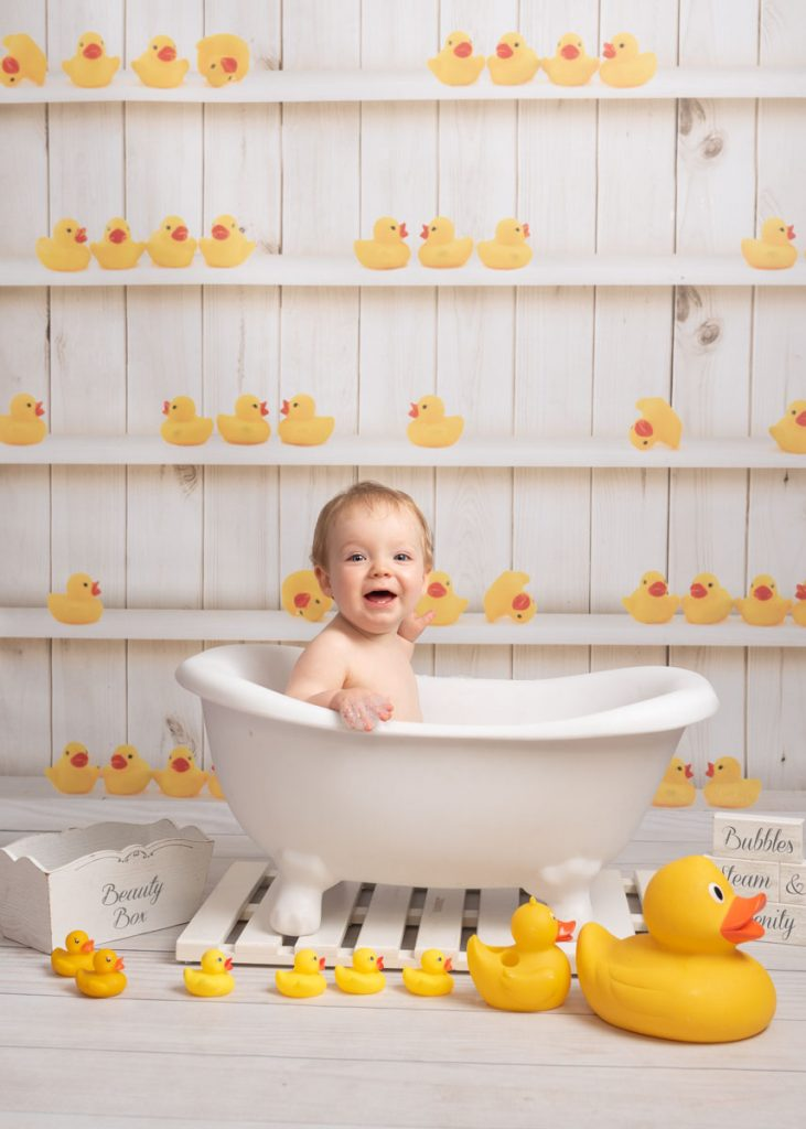 yellow ducks and little boy soaking in the tub
