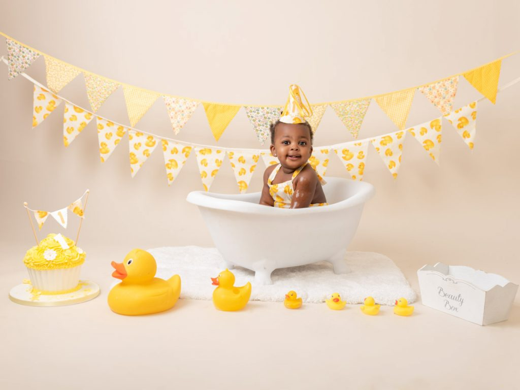smiling toddler in a prop bath with yellow ducks and a yellow cake
