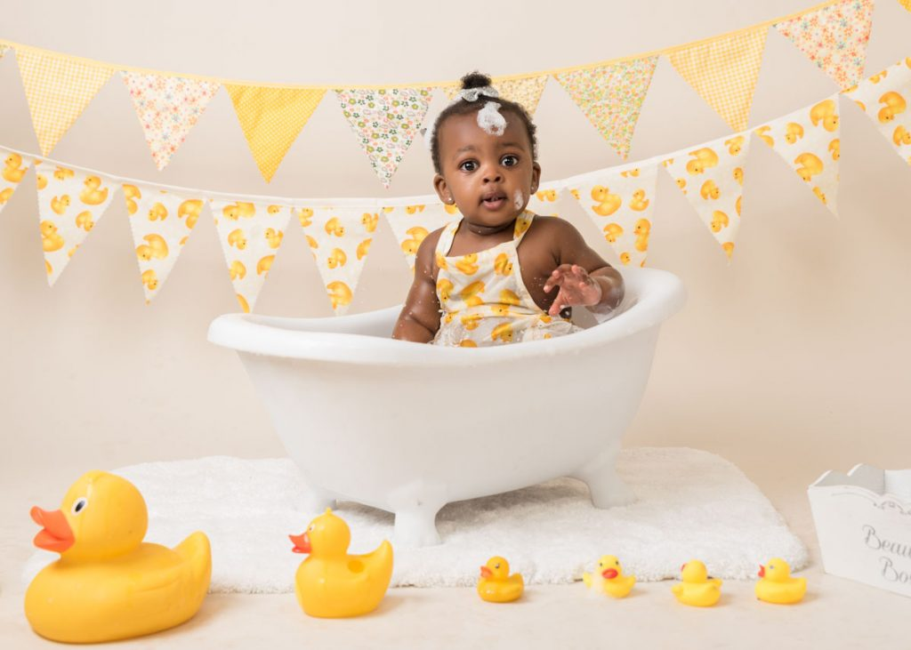 yellow themed bathtub and duck with a lovely toddler
