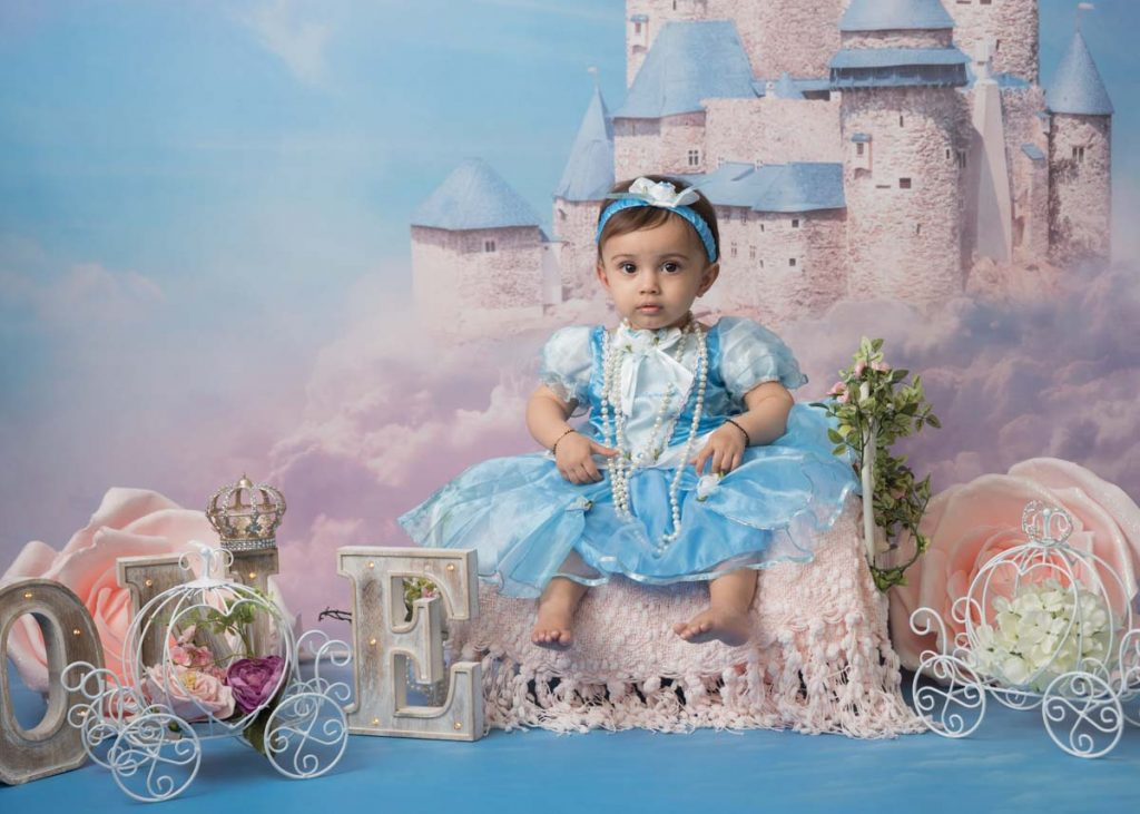 baby girl in a blue dress in front a of a fairy-tale castle