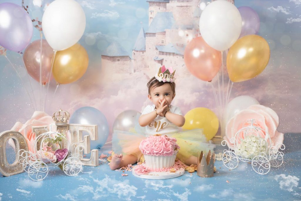 baby in a crown for her birthday with a large pink cake and balloons