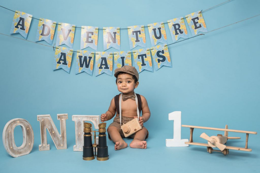 baby boy with large binoculars for a sitter photography session