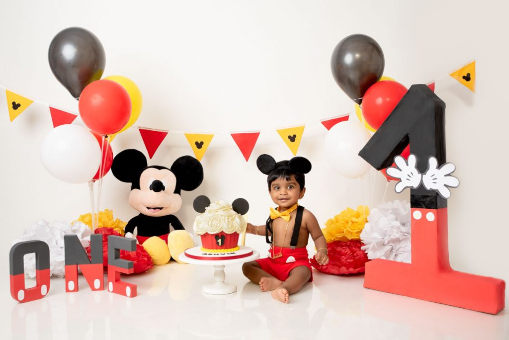 Asian baby boy in Mickey Mouse clothes for a birthday cake smash photoshoot