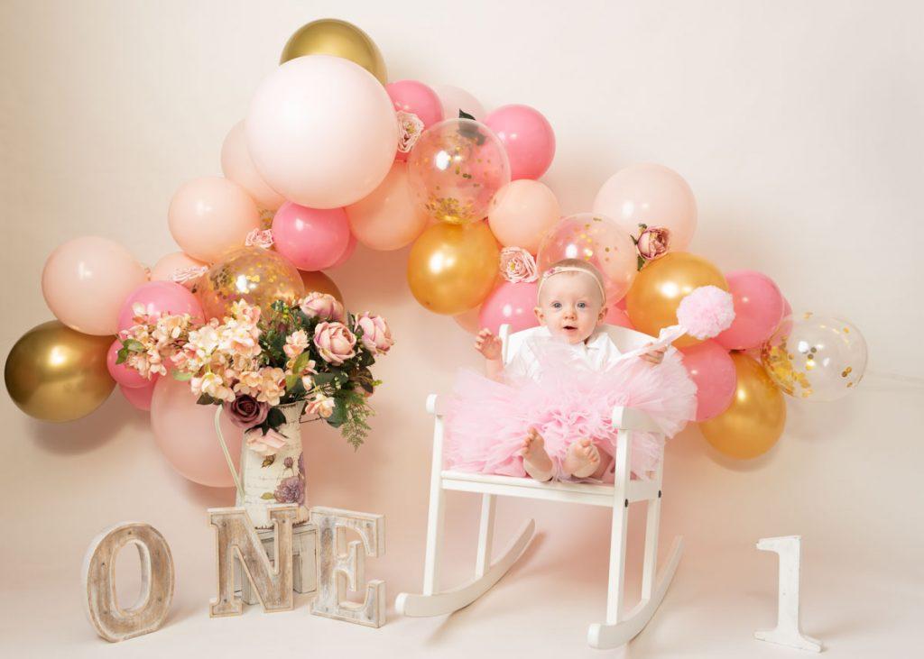 baby girl in a big fluffy dress beside flowers