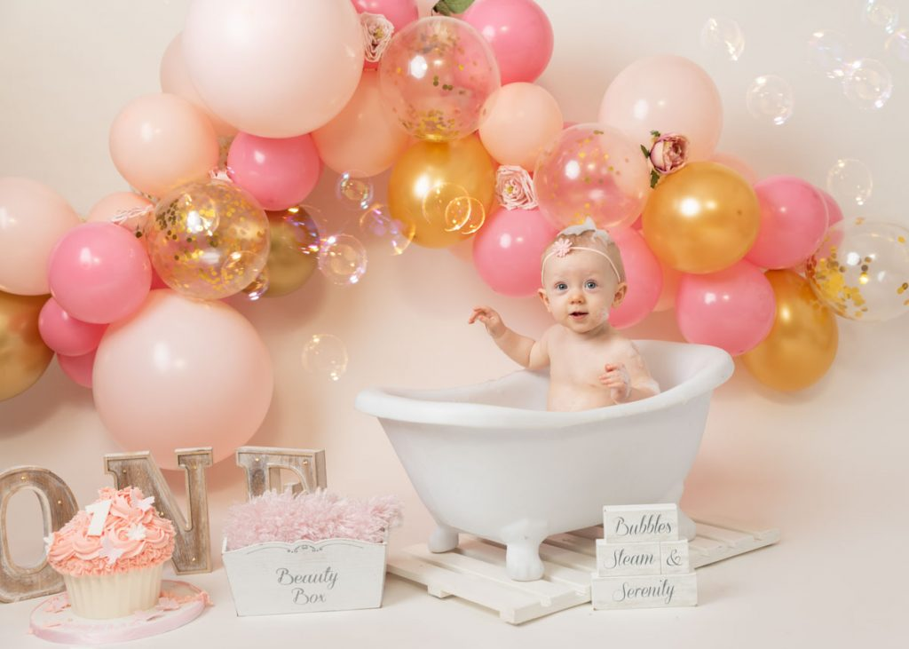 blonde baby girl in a bath with balloons behind her