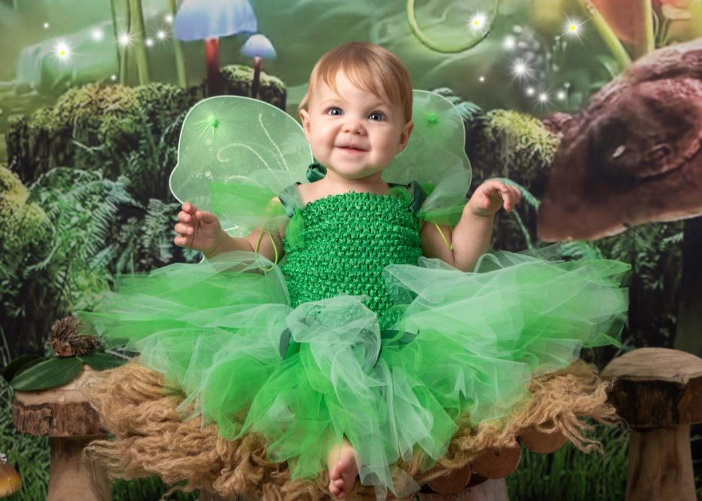 baby girl with blue eyes in a green fairy outfit