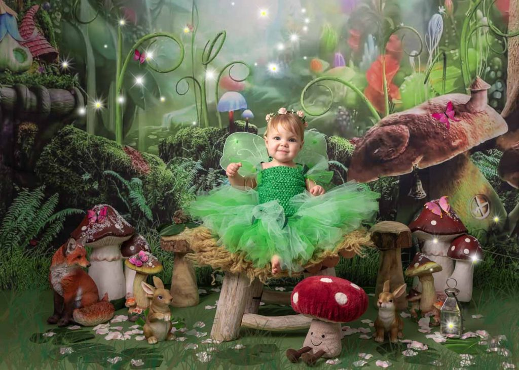 baby girl dressed as a fairy in a green frilly dress for baby sitter photography