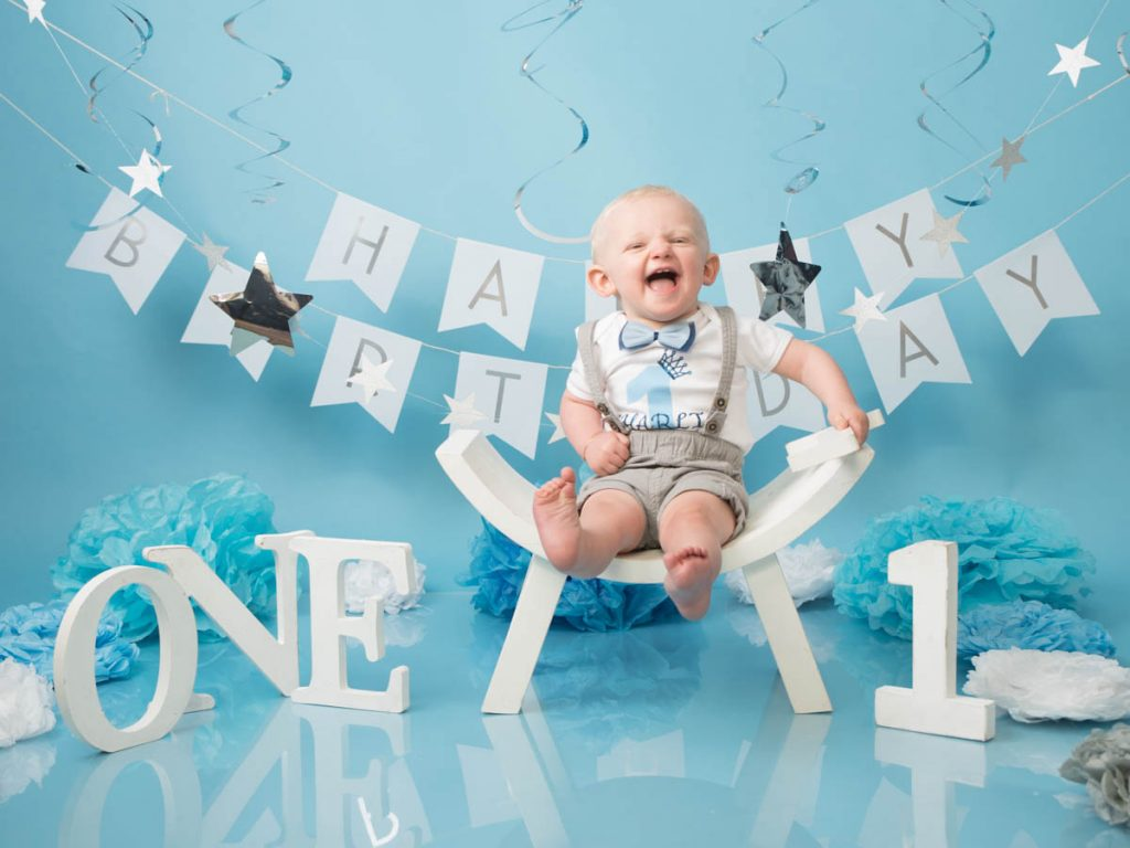 laughing baby boy on a white seat in a blue baby photography studio