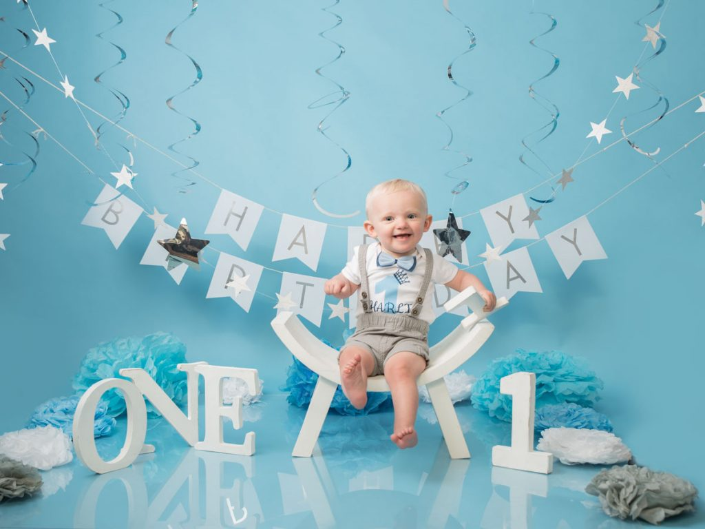 smiling baby boy on a white seat in a blue baby photography studio