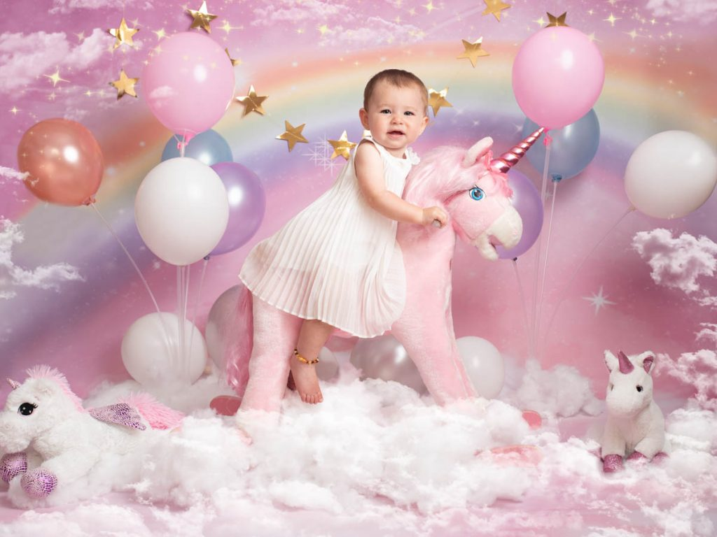 baby riding on a unicorn with balloons