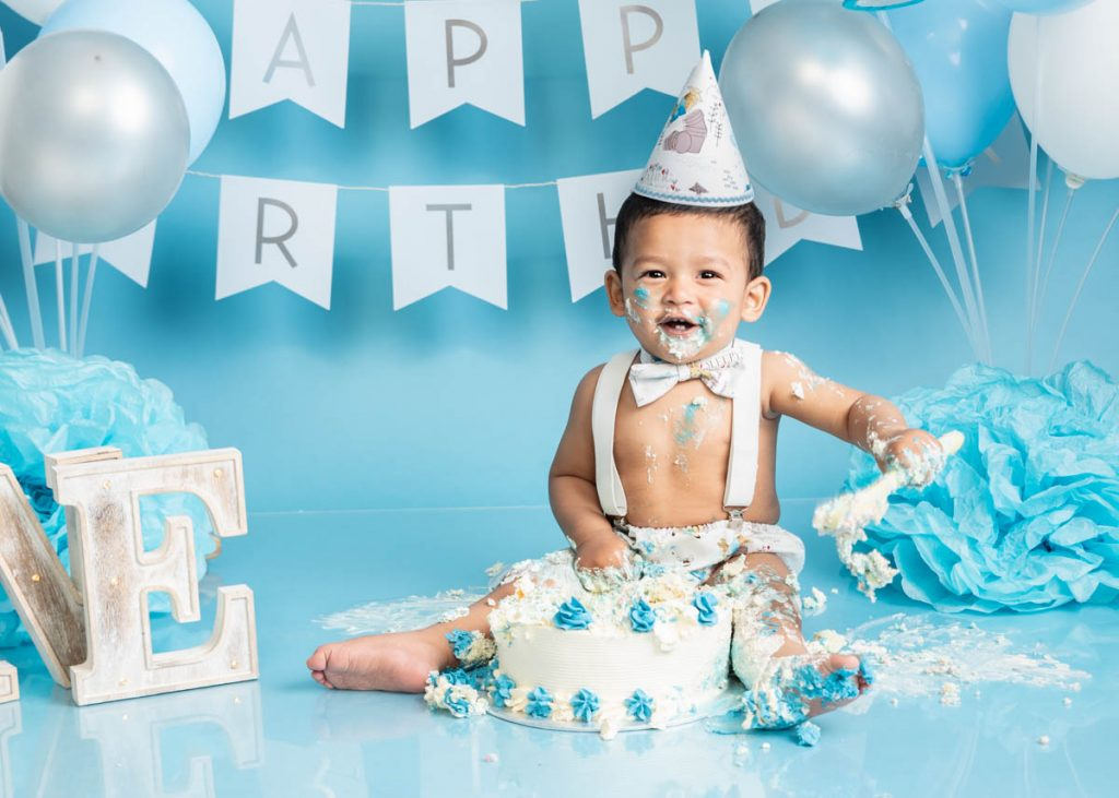 baby boy enjoying smashing a cake in a bowtie and cone hat