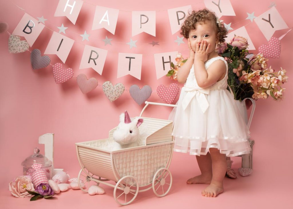 baby girl looking surprised at a unicorn in a pram in her birthday baby photography session