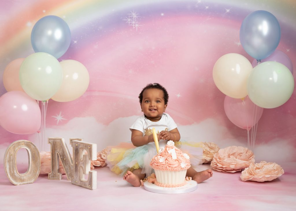 Asian baby in a frilly dress with a giant birthday cake for a cake smash photoshoot