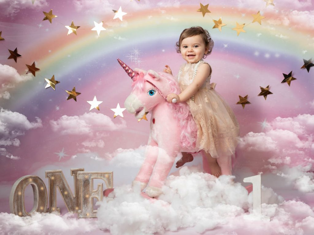 baby girl riding a unicorn in a sitter photography session