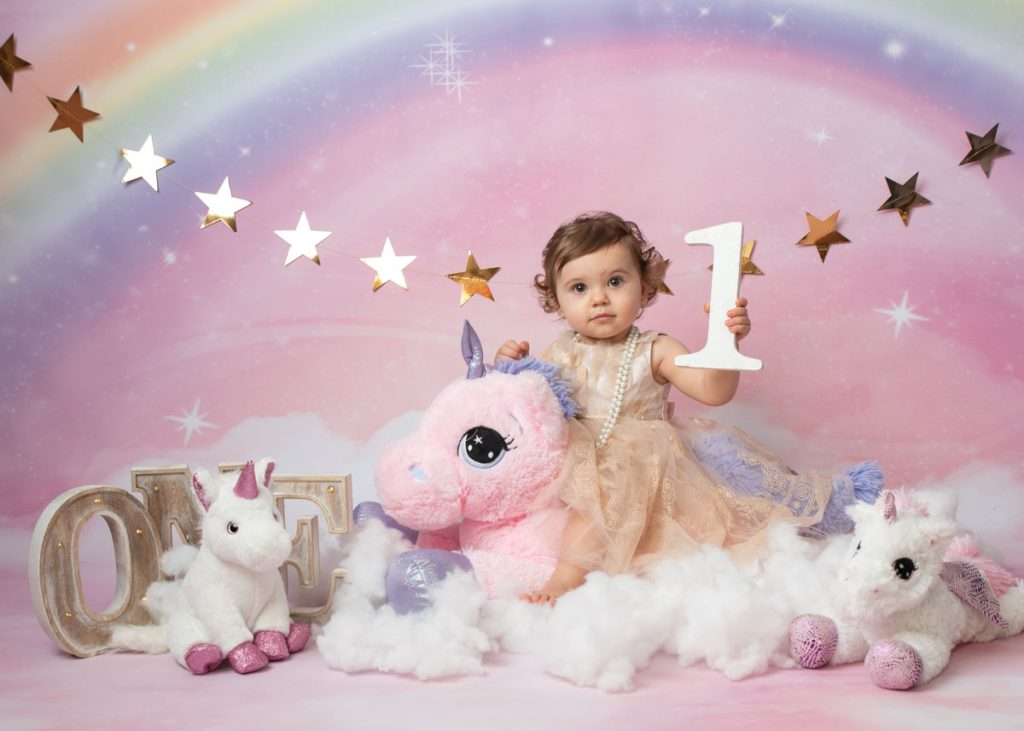 baby girl holding the number one and sitting on a unicorn