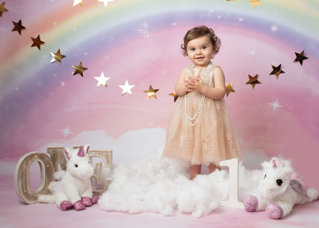 baby girl with curly hair wearing a gold dress and pearls for her birthday baby photography session