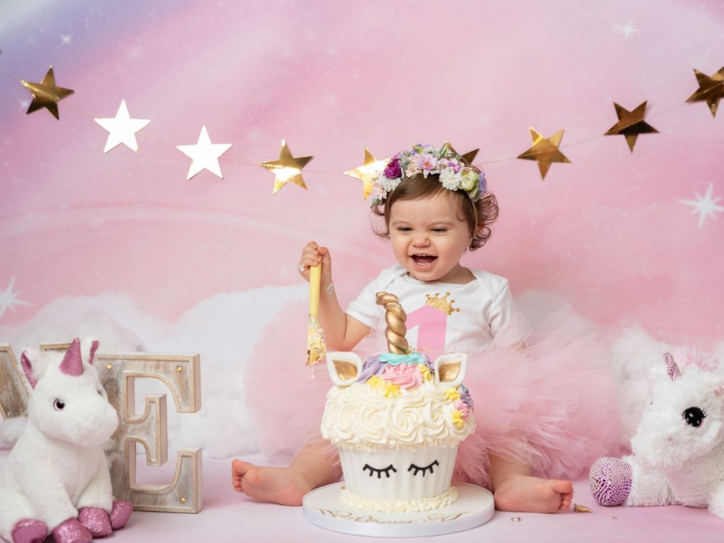 baby girl happy to be doing a cake smash photoshoot