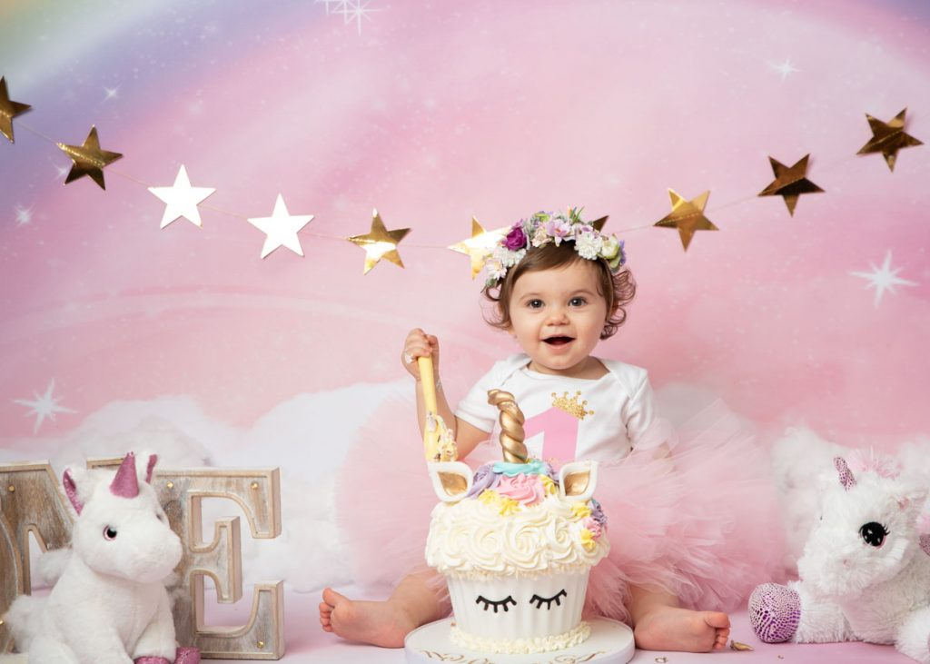 baby girl with flowers in her hair and a unicorn cake for cake smash photoshoot