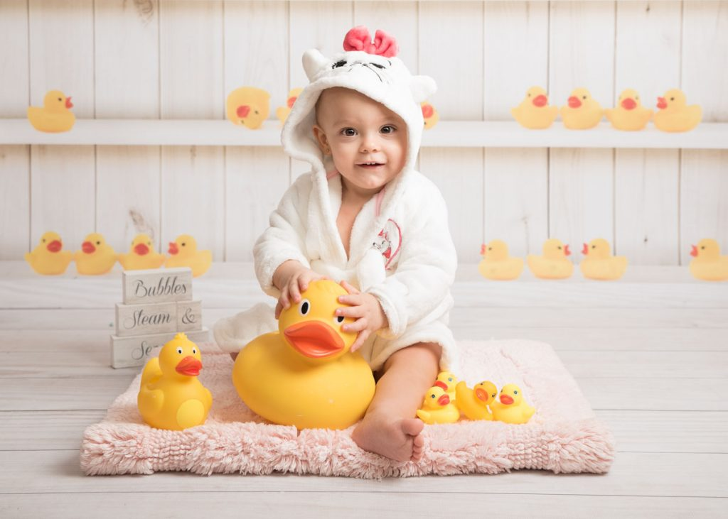 baby in a bathrobe with rubber ducks