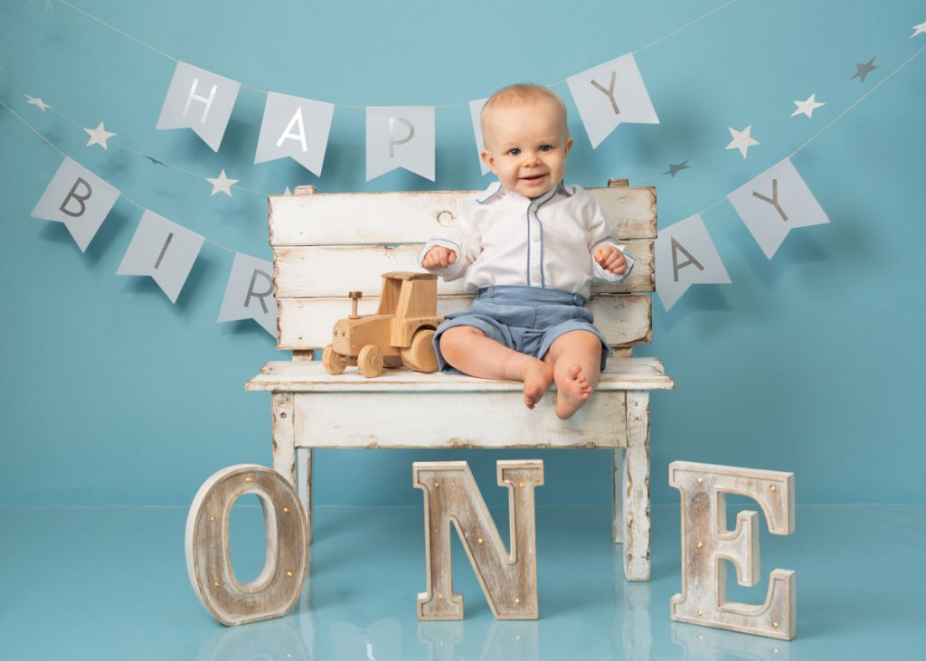 baby boy on a white bench for a sitter photography
