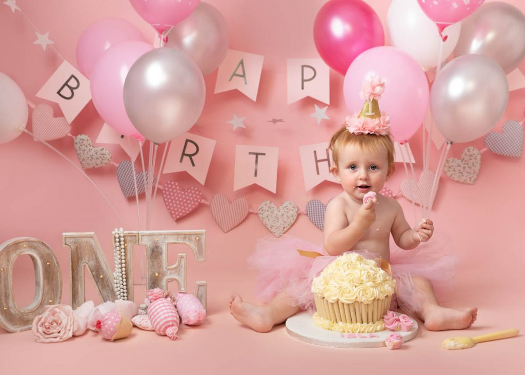 baby in a tutu with a giant cupcake for a cake smash photography session
