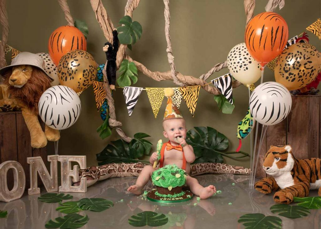 baby with stuffed tigers and lions sitting for cake smash photos