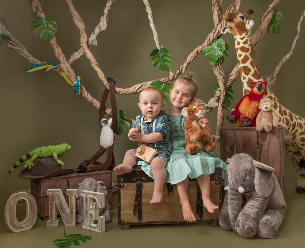 a brother and sister in the family photoshoot studio with lots of stuffed animals