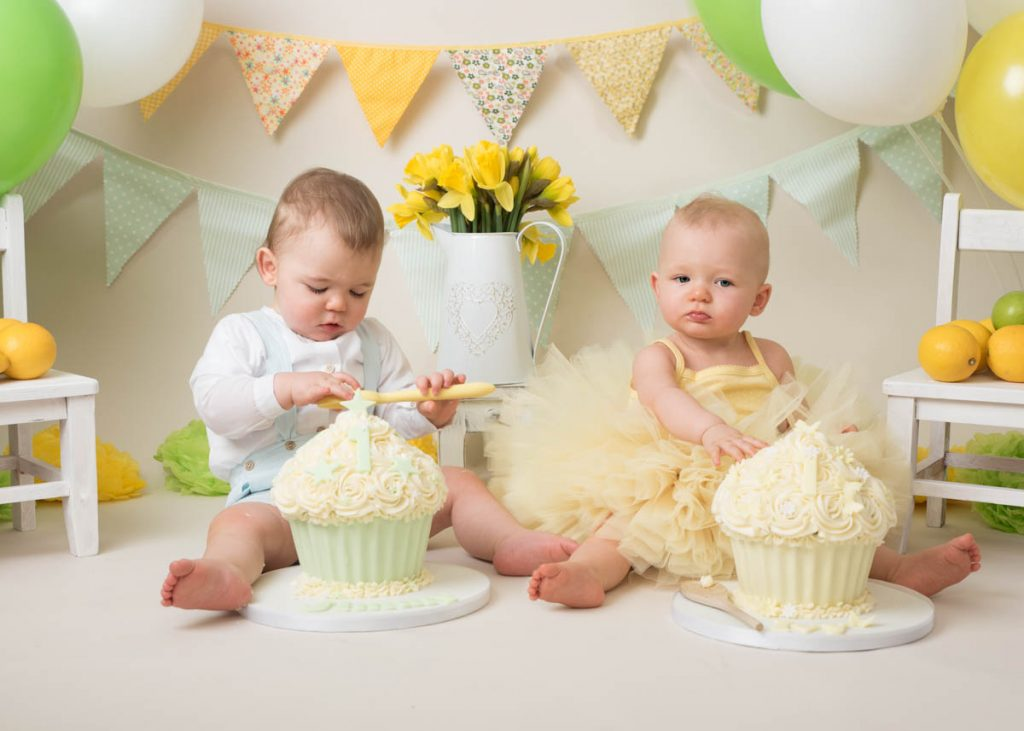 baby boy eating cake and baby girl with giant cupcake