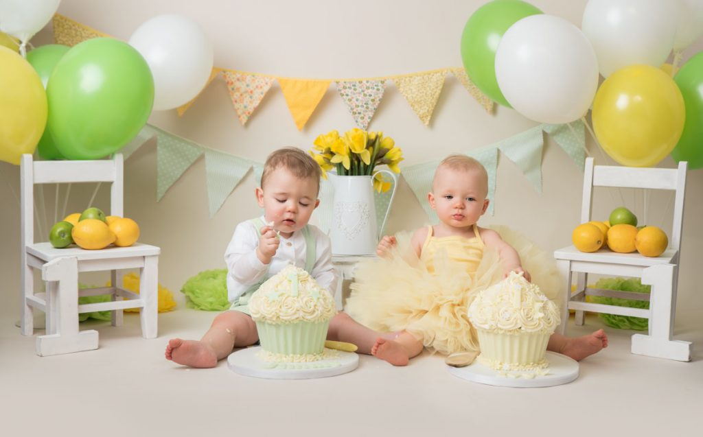 cake smash photos of boy and girl babies with giant cupcakes