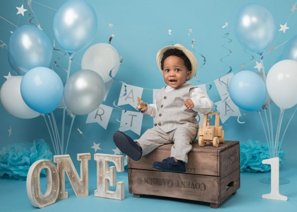 afro-Caribbean boy in a suit and hat sitting on a crate for baby photos