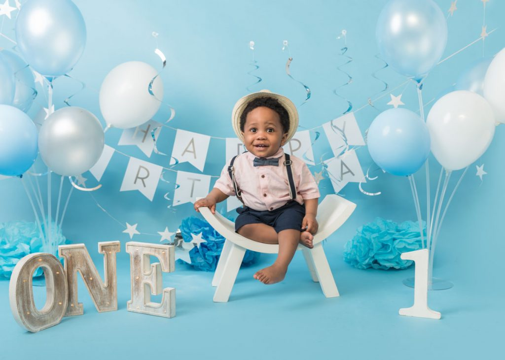 afro Caribbean boy in a hat and bowtie for a birthday baby photoshoot