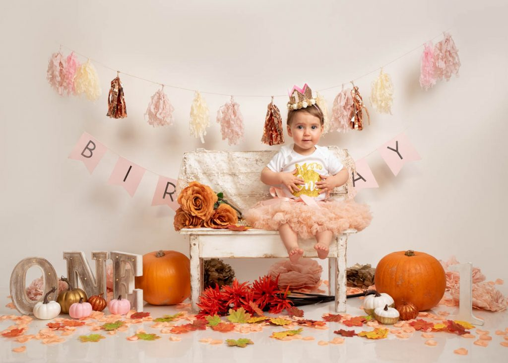 baby girl in a frilly dress and crown for her birthday baby photography session