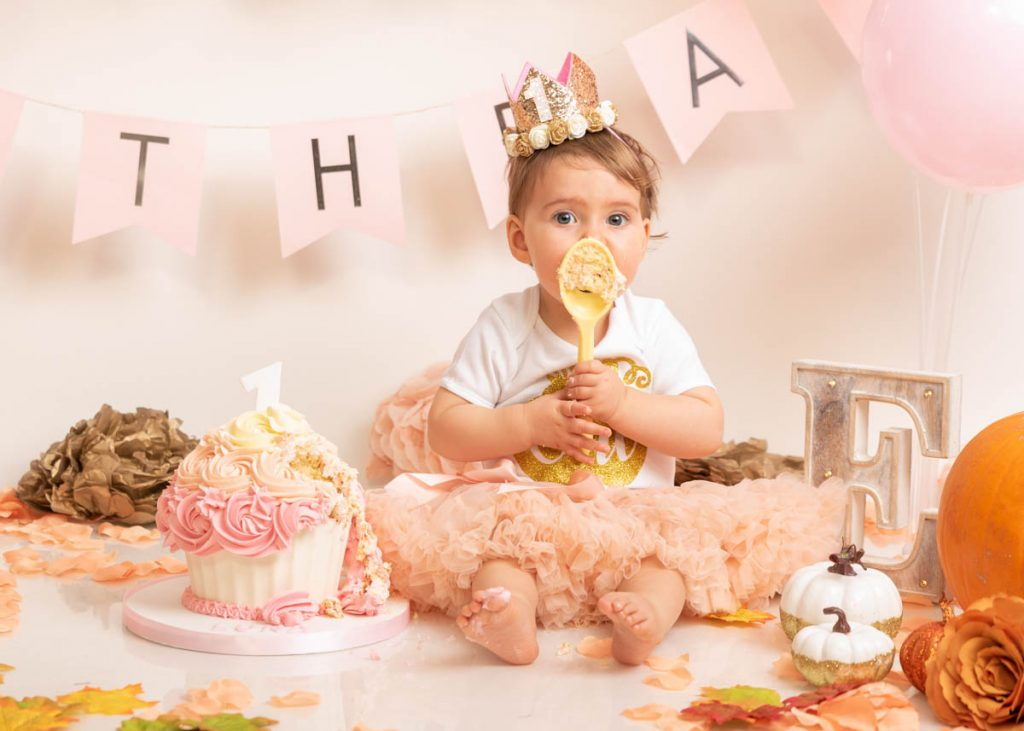 baby girl in a frilly dress licking a cake spoon