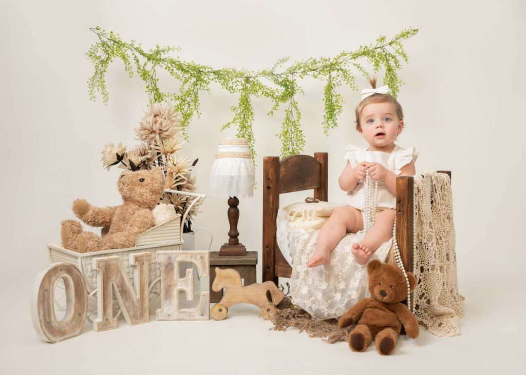 baby girl with hair in a bow and a string of pearls for sitter photography session