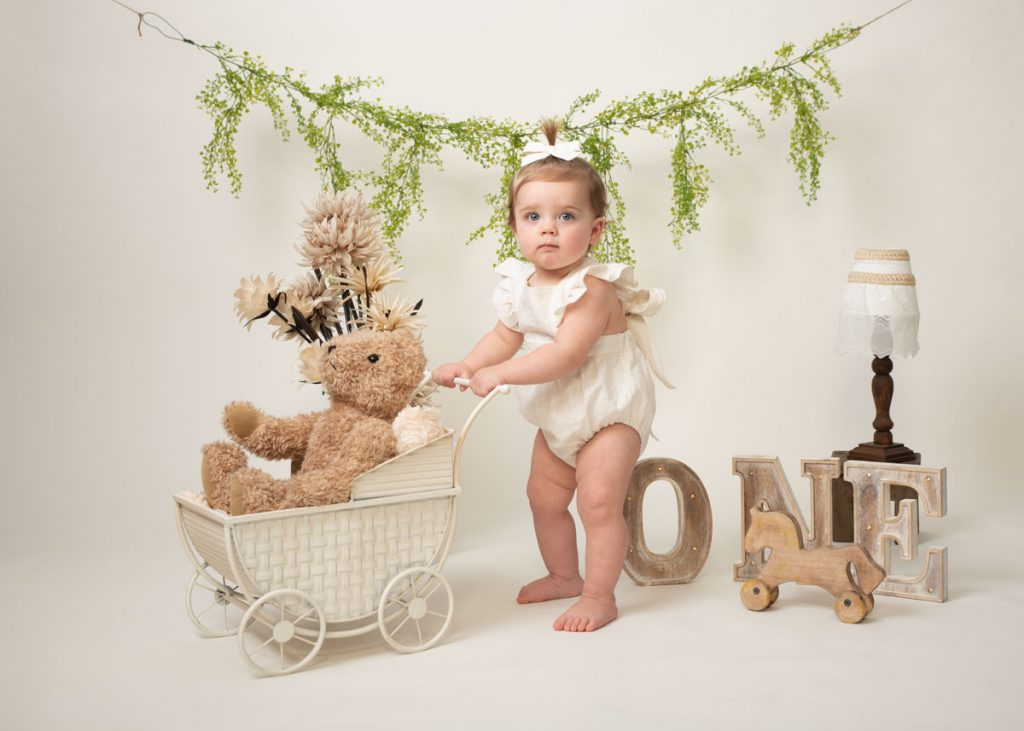 baby girl with a bow in her hair and a vintage pram for baby photos