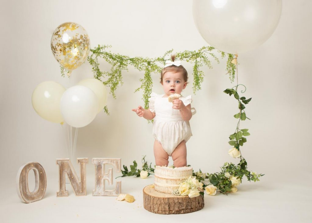 baby girl with hair in a bow and a piece of cake for her birthday cake smash photos