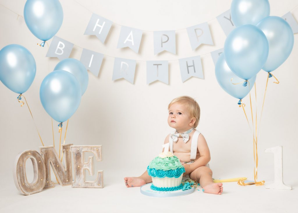 blonde boy in braces sitting with a blue cake for a cake smash photography session