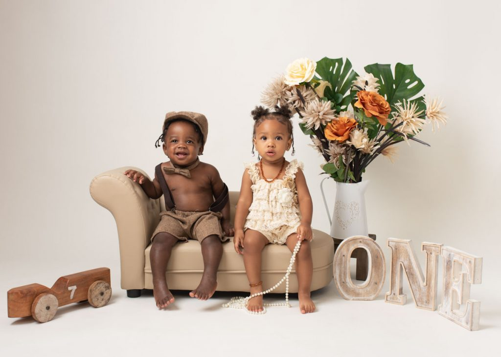 Girl and boy twins sitting on a brown sofa for sitter session photography