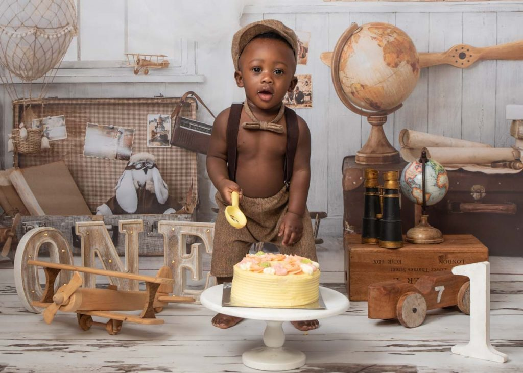 Young boy in a hat ready for cake smash photos