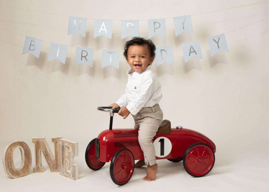 first birthday photoshoot riding a car