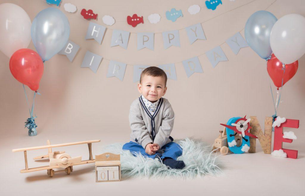 little boy in a lovely little sweatshirt enjoying his first birthday