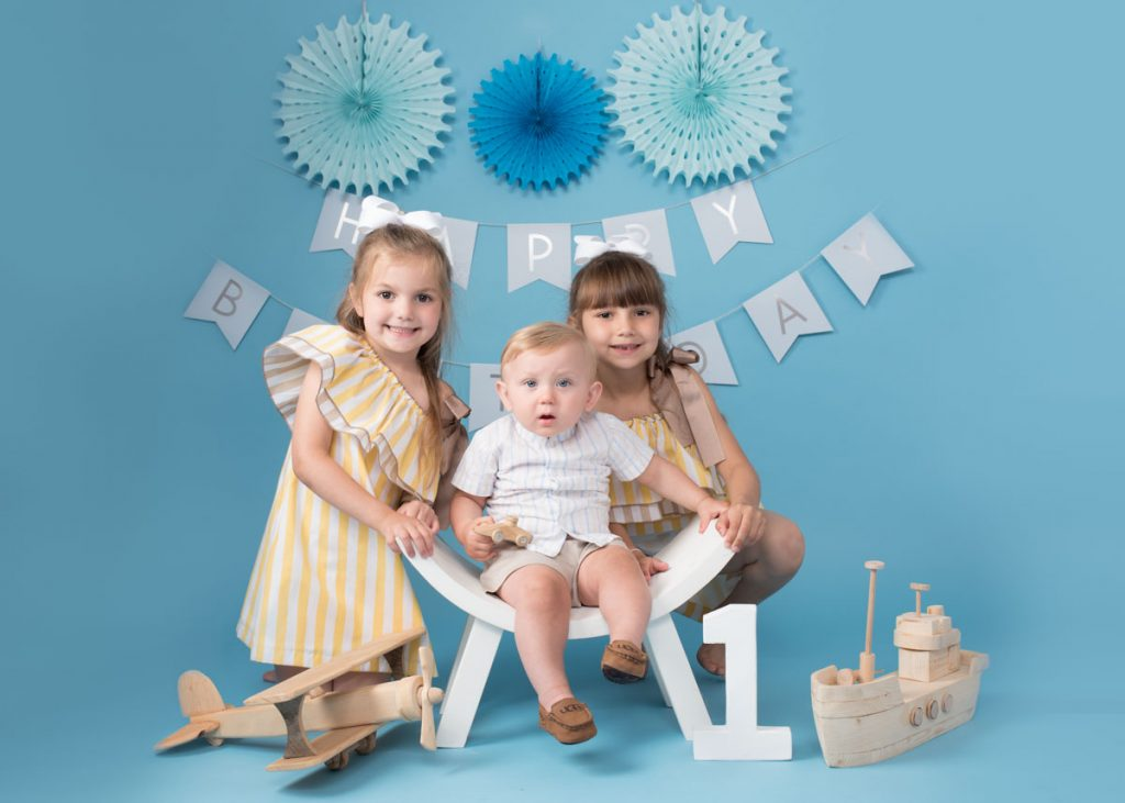 sisters and youngest brother photoshoot surrounded by wooden toys