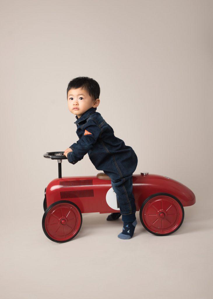 little boy playing on a car